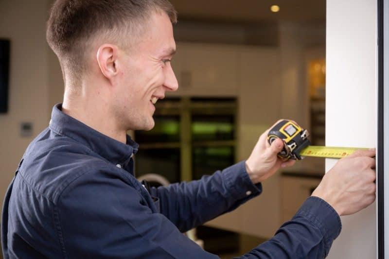 measured building surveyor using a tape measure