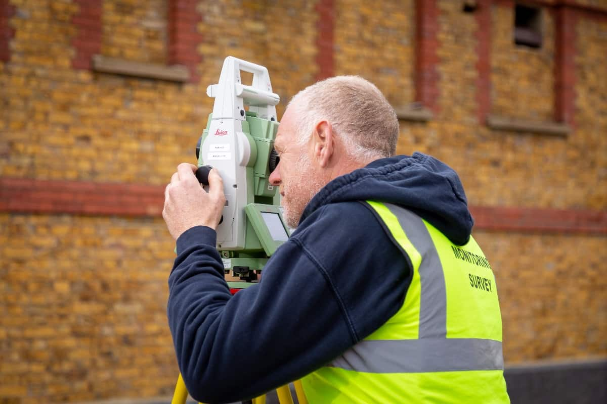 Land surveyor using a leica total station measuring a wall