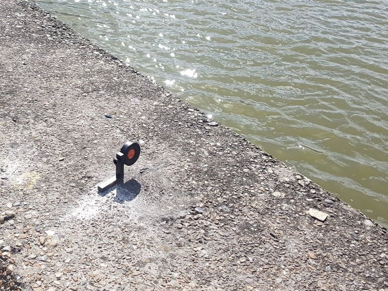 Monitoring survey prism on a river wall.